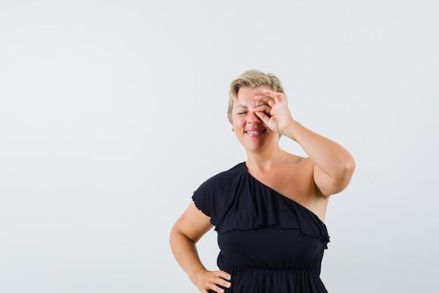 Betoverende vrouw die ok gebaar op oog in zwarte blouse toont