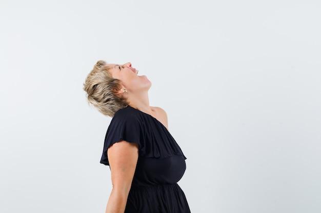 Betoverende vrouw die omhoog kijkt terwijl schreeuwend in zwarte blouse en gek kijkt