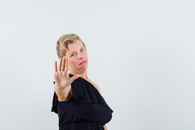 Betoverende vrouw die stopgebaar in zwarte blouse toont en ernstig kijkt