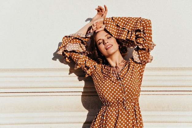 Betoverende vrouw in het vintage kleding stellen met gesloten ogen. buitenfoto van ontspannen vrouwelijk model in bruine kledij.