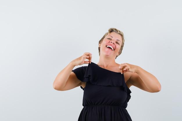 Betoverende vrouw in zwarte blouse die haar blouse knijpt en heel kijkt