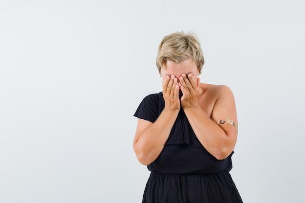 Betoverende vrouw in zwarte blouse die handen op gezicht houdt en droevig kijkt