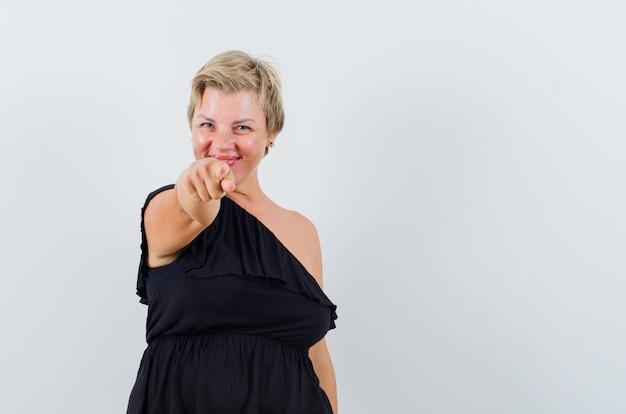 Betoverende vrouw in zwarte blouse die op camera richt en tevreden kijkt