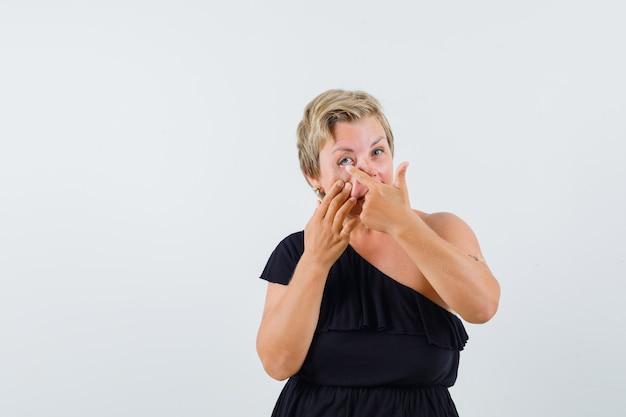 Betoverende vrouw in zwarte blouse die op haar oog richt en geconcentreerd kijkt