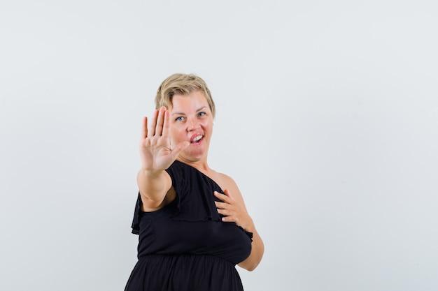 Betoverende vrouw in zwarte blouse die stopgebaar toont en terughoudend kijkt