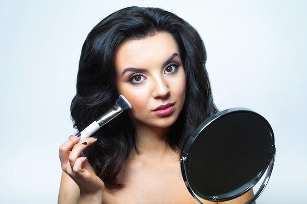 Betoverende vrouw met gezichts cosmetica.
