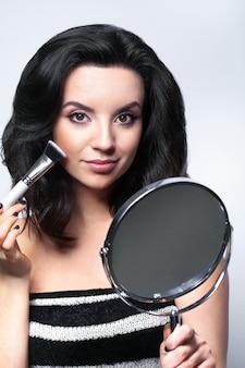 Betoverende vrouw met gezichtsschoonheidsmiddelen en spiegel