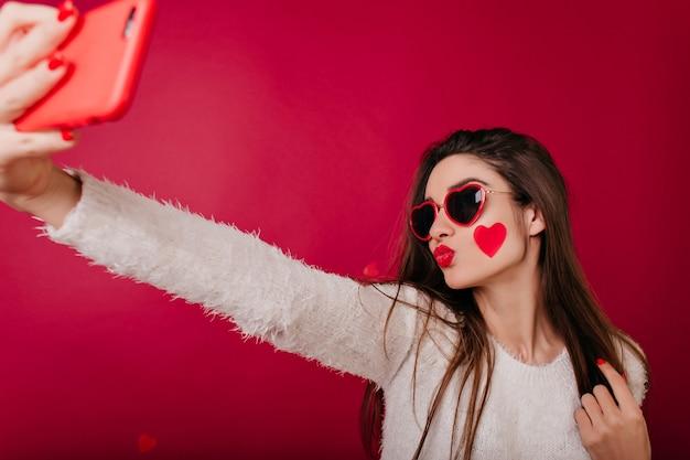 Betoverende vrouw met hart op wang poseren met kussende gezichtsuitdrukking