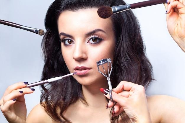 Betoverende vrouw met make-uphulpmiddelen
