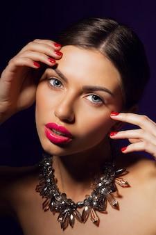 Betoverende vrouw met rode lippen, kleurrijke nagels en perfecte huid