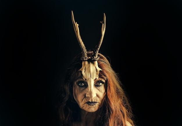 Betovering en magie. oude heks met dierlijke schedel en gewei. oma heks, halloween.