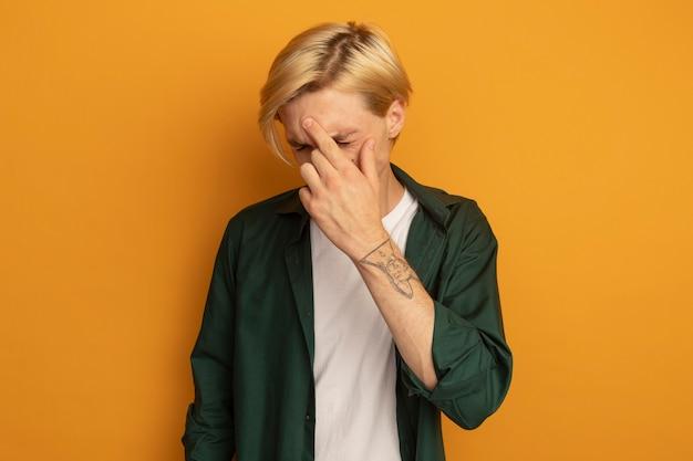 Betreurd met gesloten ogen jonge blonde kerel die groen t-shirt draagt dat hand op voorhoofd legt