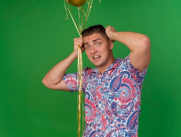 Betreurde jonge feestman met ballonnen en pakte het hoofd met een bril geïsoleerd op groen