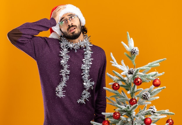Betreurde jonge knappe kerel die in de buurt van de kerstboom staat met een kerstmuts met een guirlande op de nek en legt de hand op het voorhoofd geïsoleerd op een oranje muur