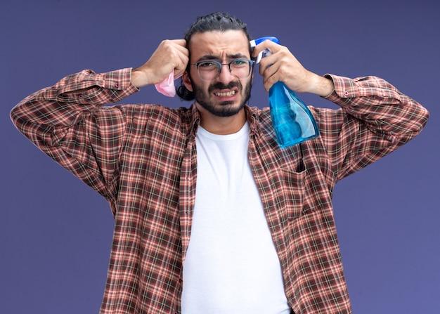 Betreurde jonge knappe schoonmaakster die de spuitfles van de t-shirtholding met lap rond gezicht draagt dat op blauwe muur wordt geïsoleerd