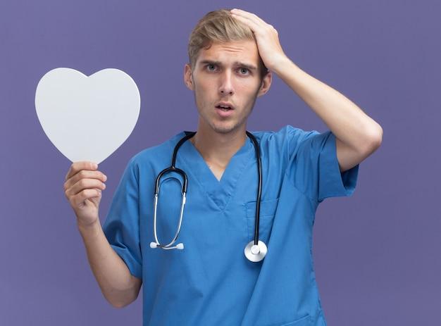 Betreurde jonge mannelijke arts die artsenuniform met een stethoscoop draagt die de doos van de hartvorm houdt die hand op hoofd zet dat op blauwe muur wordt geïsoleerd