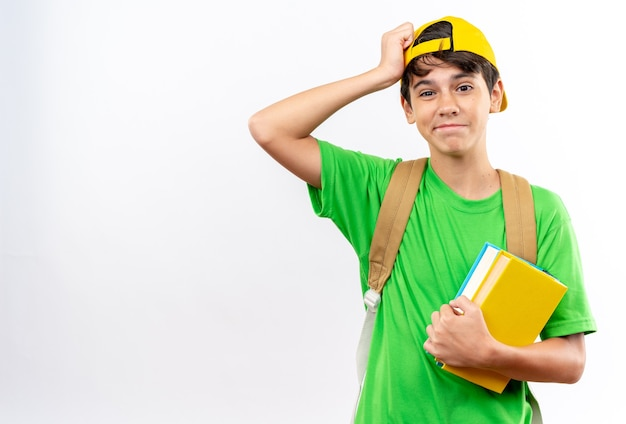 Betreurde jonge schooljongen die een rugzak draagt met een pet die boeken vasthoudt en hand op het voorhoofd legt dat op een witte muur wordt geïsoleerd