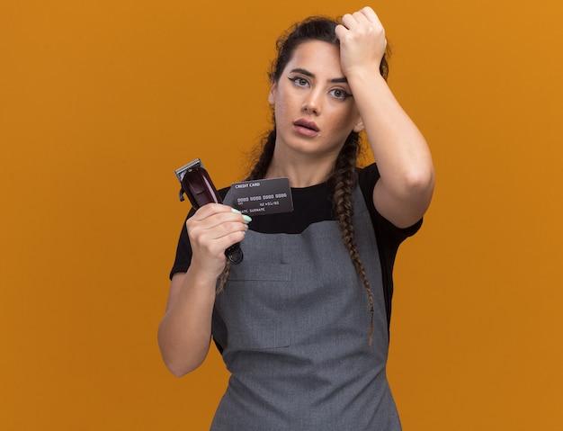 Betreurde jonge vrouwelijke kapper in uniform bedrijf creditcard en tondeuse hand zetten voorhoofd geïsoleerd op oranje muur met kopie ruimte