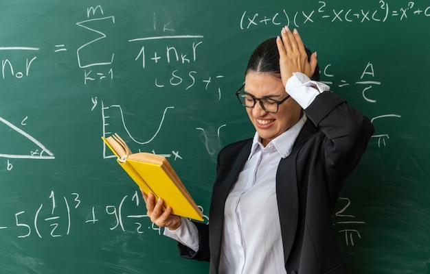 Betreurde jonge vrouwelijke leraar die een bril draagt die vooraan het leesboek van het schoolbord staat en de hand op het hoofd zet in de klas
