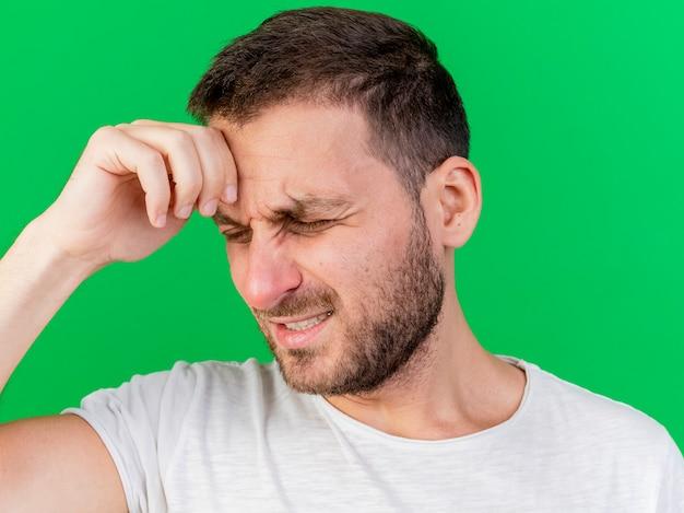 Betreurde jonge zieke man hand op voorhoofd geïsoleerd op groen te zetten