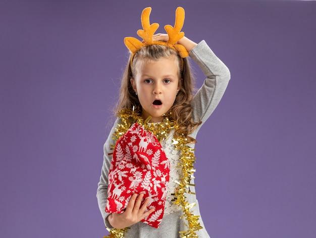 Betreurde klein meisje met kersthaar hoepel met guirlande op nek met kersttas en hand op hoofd geïsoleerd op blauwe muur