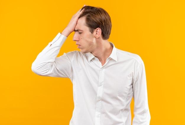 Betreurde met gesloten ogen jonge knappe kerel die wit overhemd draagt dat hand op voorhoofd legt dat op oranje muur wordt geïsoleerd