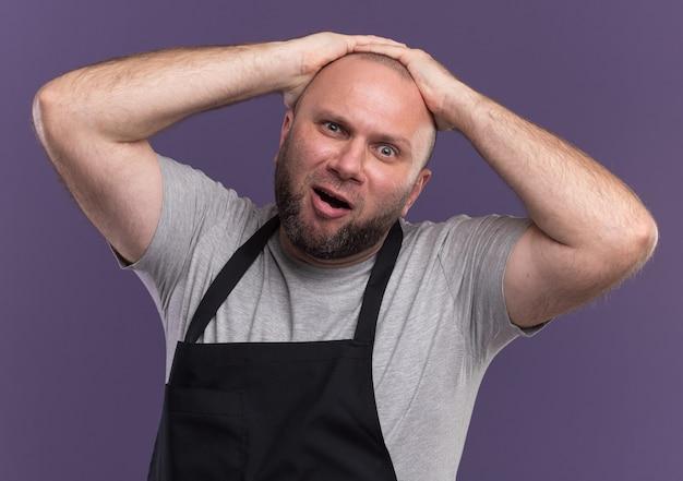 Betreurde slavische mannelijke kapper van middelbare leeftijd in uniform greep hoofd geïsoleerd op paarse muur