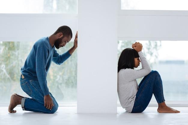 Betreuren. emotionele trieste jongeman medelijden met het beledigen van zijn mooie vriendelijke vriendin