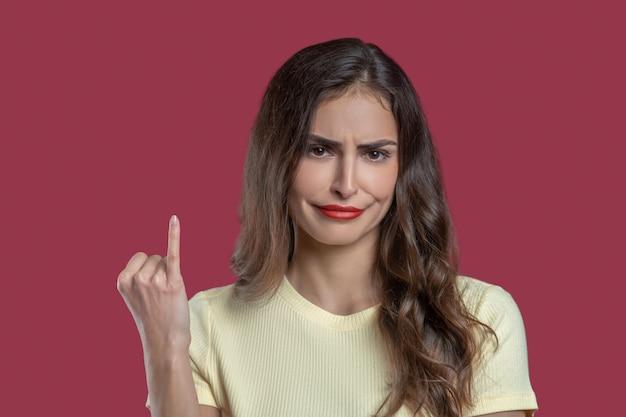 Betreuren. jonge langharige vrouw met rode lippen expressieve blik met spijtige grimas die pink toont