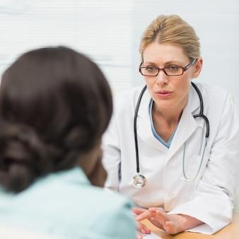 Betrokken arts die aan haar patiënt spreekt