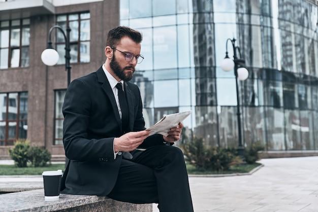 Betrokken bij lezen. knappe jongeman in volledig pak die een krant leest