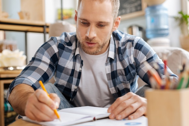 Betrokken bij werk. knappe creatieve doordachte man aan tafel zitten en notities maken terwijl hij zich op zijn werk concentreert
