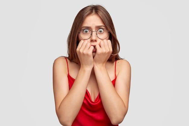 Betrokken brunette jonge vrouw poseren tegen de witte muur