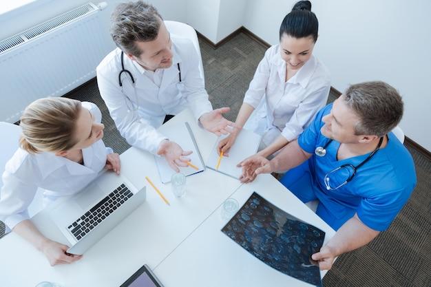 Betrokken energetisch bekwame oncologen die in de examenkast werken en mrt-foto's bekijken terwijl ze discussiëren en gadgets gebruiken