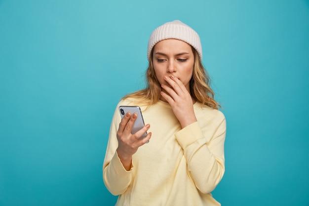 Betrokken jong meisje dat de winterhoed draagt die hand op mond houdt en mobiele telefoon bekijkt