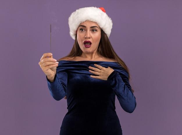 Betrokken jong mooi meisje dat een blauwe jurk en kerstmuts draagt en naar wonderkaarsen kijkt die de hand zelf zetten geïsoleerd op paarse muur