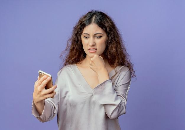 Betrokken jong mooi meisje houden en kijken naar telefoon