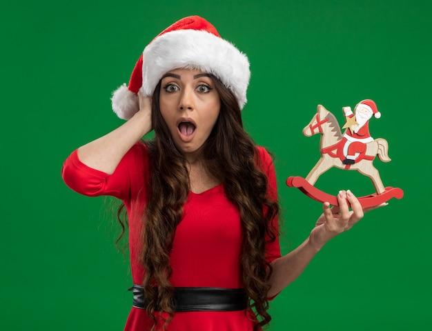 Betrokken jong mooi meisje met kerstmuts bedrijf santa op hobbelpaard beeldje hand houden op het hoofd kijken camera geïsoleerd op groene achtergrond