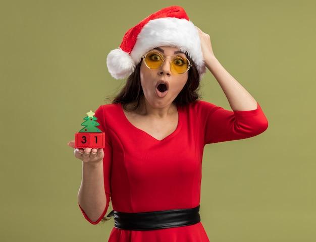 Betrokken jong mooi meisje met kerstmuts en bril bedrijf kerstboom speelgoed met datum hand op het hoofd kijken camera geïsoleerd op olijf groene achtergrond