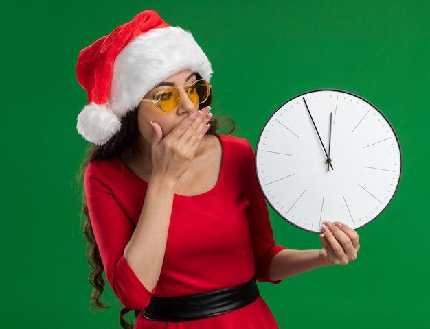 Betrokken jong mooi meisje met kerstmuts en bril houden en kijken naar klok hand houden op mond geïsoleerd op groene achtergrond