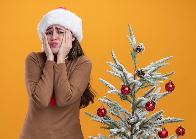Betrokken jong mooi meisje met kerstmuts met stropdas staande in de buurt van kerstboom handen op wangen geïsoleerd op een oranje achtergrond te zetten