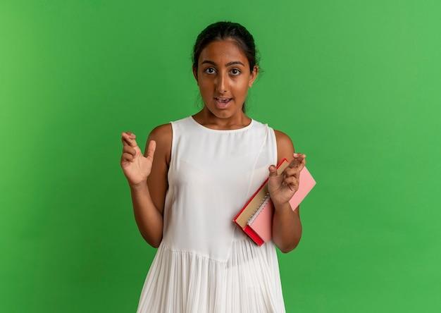 Betrokken jong schoolmeisje met boek met notitieboekje en vingers kruisen