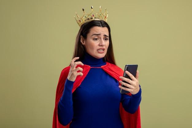Betrokken jong superheld meisje dragen kroon houden en kijken naar telefoon geïsoleerd op olijfgroen
