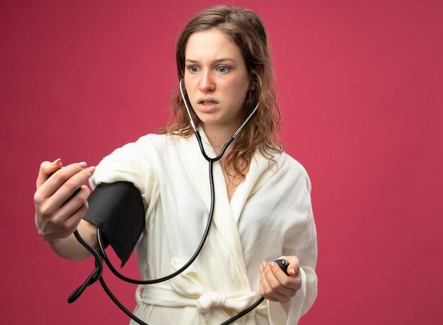 Betrokken jong ziek meisje dat een wit gewaad draagt dat haar eigen druk meet met een bloeddrukmeter die op roze wordt geïsoleerd
