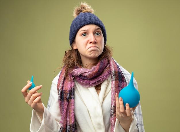 Betrokken jong ziek meisje dat een wit gewaad en een wintermuts met een sjaal draagt die in geruite klysma's wordt verpakt die op olijfgroen worden geïsoleerd