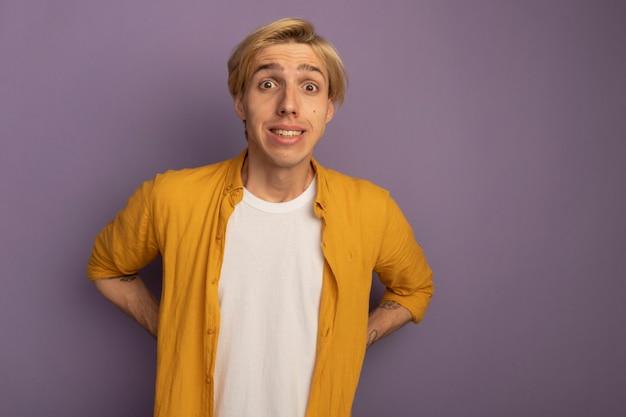 Betrokken jonge blonde kerel die gele t-shirt draagt die handen op taille zet