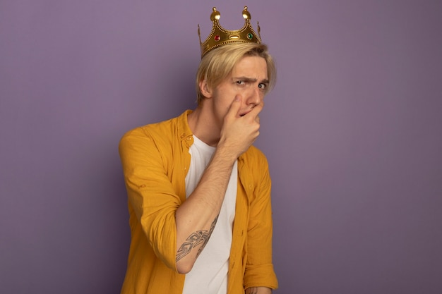 Betrokken jonge blonde kerel die gele t-shirt en kroon overdekte mond met hand draagt die op paars wordt geïsoleerd