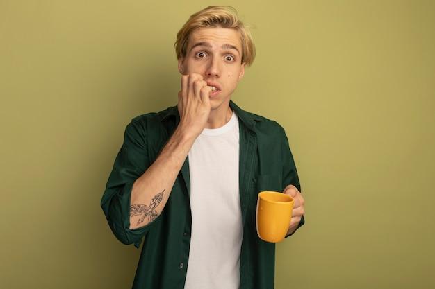 Betrokken jonge blonde kerel die groene t-shirt draagt die kop thee houdt en nagels bijt