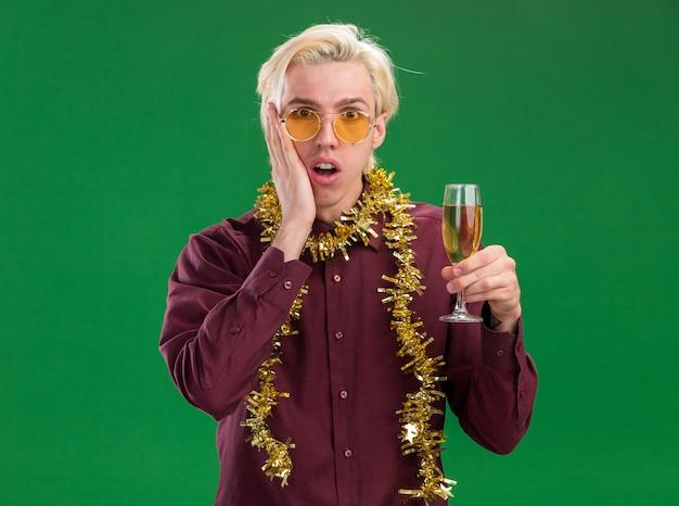 Betrokken jonge blonde man die een bril met een klatergoudslinger om de nek draagt en een glas champagne houdt die hand op het gezicht houdt dat op groene muur wordt geïsoleerd
