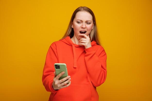 Betrokken jonge blonde vrouw die en mobiele telefoon bekijkt die hand op kin houdt